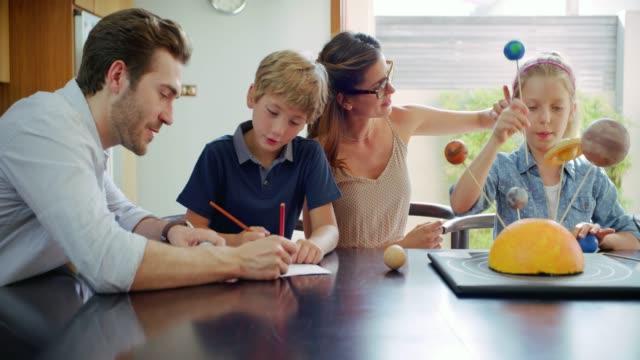 vídeos y material grabado en eventos de stock de hacer la tarea de los niños en familia - hermano