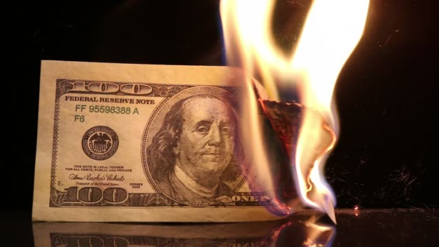 dollar bill in flames. american money burning on black background. - avidità video stock e b–roll
