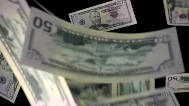 50 dollar bills fall down on a black background video