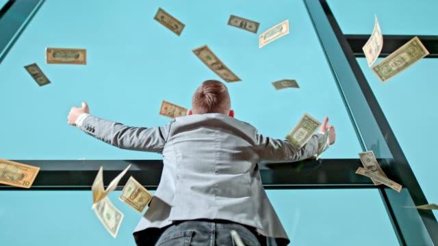 us dollar bills falling over young businessman boy at office window, super slow motion - avidità video stock e b–roll
