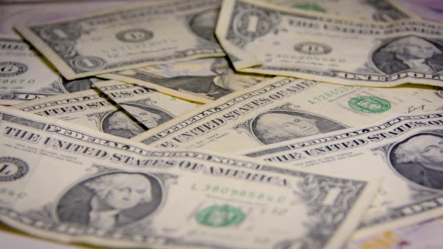 Dollar notes are moved by a small breeze and below appears the chinese yuan video