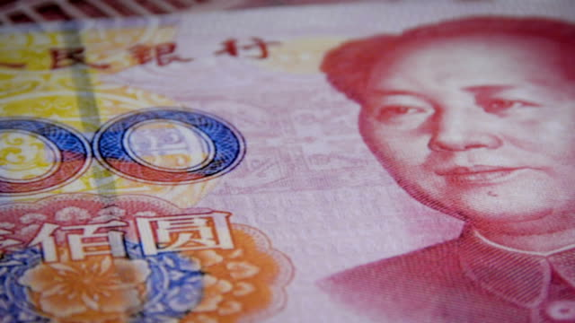 Dollar notes placed over a chinese yuan bill video