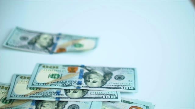 US dollars banknotes falling on white surface. Wages, arnings, winnings video
