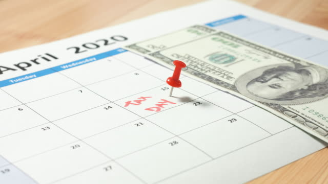 Dollars on calendar marked for tax day Red pin marked at April 15 for tax day with dollars falling on 2020 calendar. 4k footage resolution april stock videos & royalty-free footage