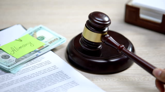 Dollars with alimony sign table, gavel striking sound block, financial support
