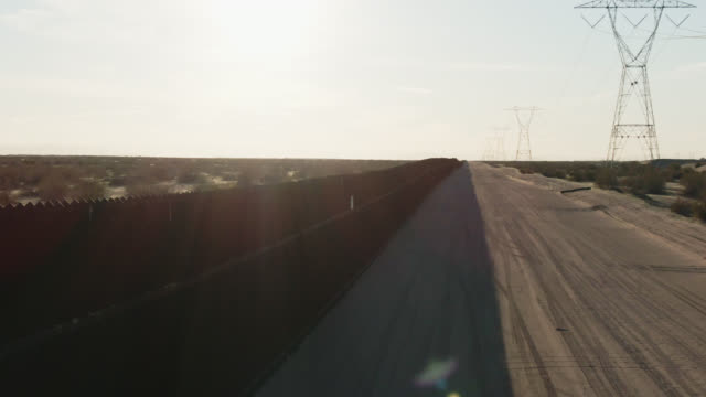 Dolly Aerial Drone Shot of Flying over the Steel-Slat Border Wall and a Dirt Road (on the US side) between Mexico and the United States on a Bright, Sunny Afternoon
