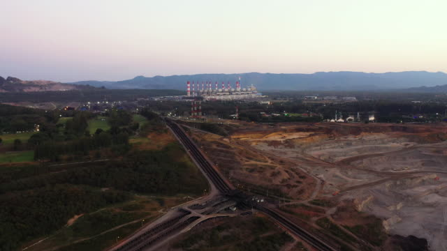 Dolly back: Lignite coal move to power station by conveyor belt in aerial view