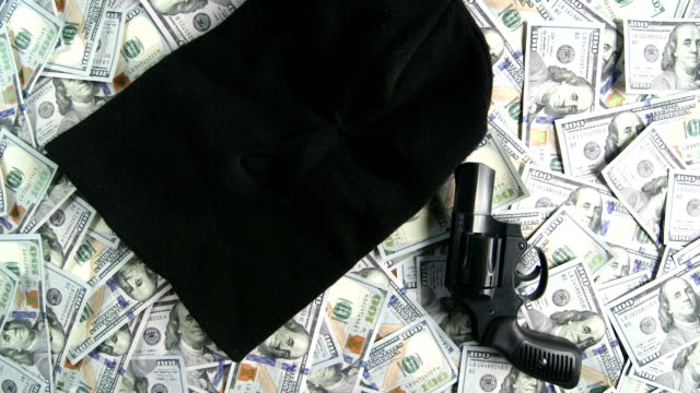 Dolly: Balaclava and gun on pile of $100 american dollar banknotes video