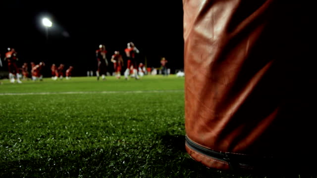 dolly behind a goalpost as football players warm up before a night time game video