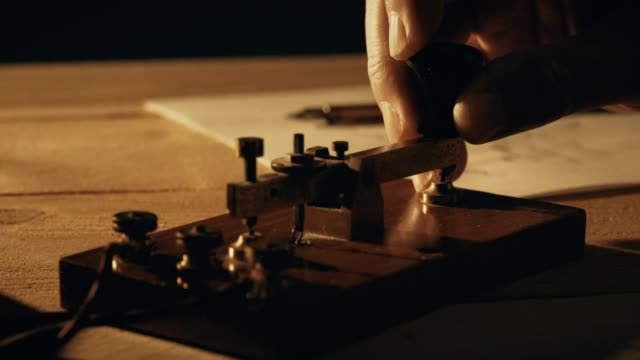 dolly closeup of a telegrapher using a morse code key