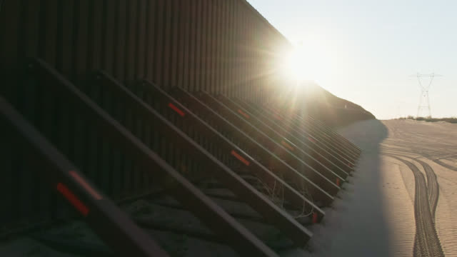 Dolly Drone Shot of the Steel-Slat Border Wall and Its Supports (on the US Side) between Mexico and the United States on a Clear, Sunny Day at Sunset