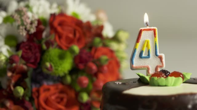 Dolly: Flower arrangement and birthday cake with burning candle number 4