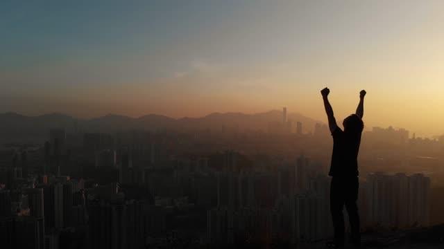vídeos de stock e filmes b-roll de dolly forward of man standing and arm raise for celebration on mountain peak. - retroiluminado