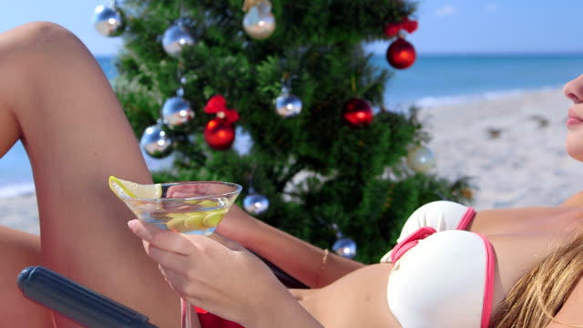 Dolly: Girl in Santa hat with martini  on tropical beach video
