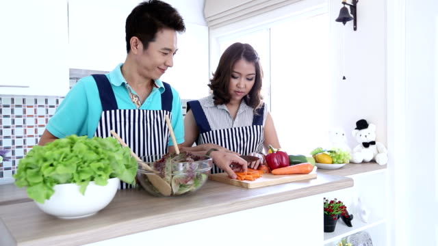 Dolly: Happy Couples preparing and cooking green vegetable salad video