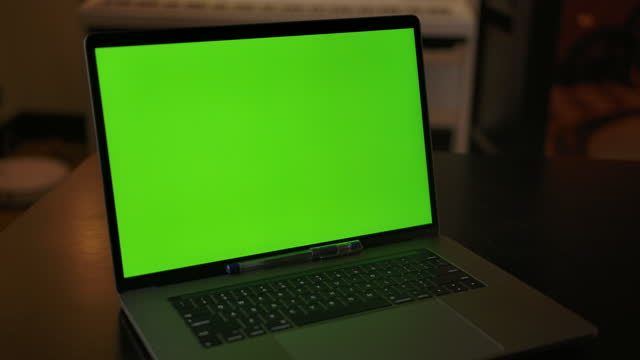 Dolly in shot of green screen laptop indoor of cozy home interior