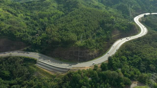 dolly ha lasciato la vista aerea della strada passando per la montagna - passo montano video stock e b–roll