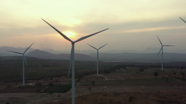 Dolly left aerial view of Wind Turbine in sunset time