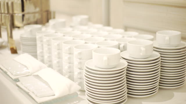 MS Dolly left Camera of White dishware stacks of clean cups and plates on the table indoors.