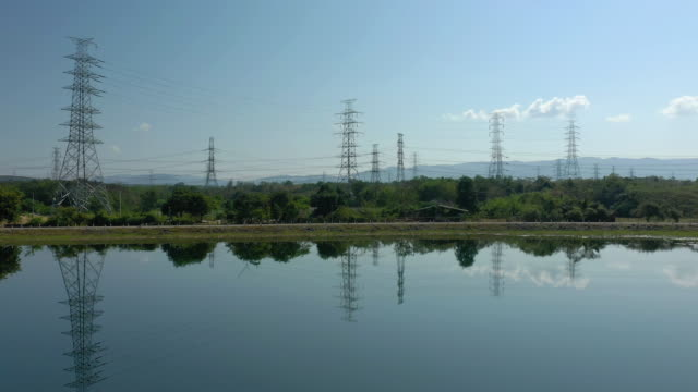 Dolly left: Reflection of electricity pylons aerial view with blue sky