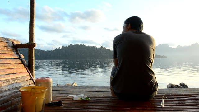 dolly : lonely man sits on Raft houses in Khao Sok National Park video
