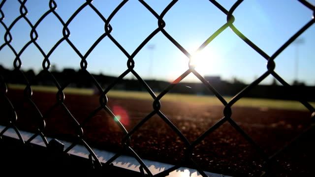 vídeos y material grabado en eventos de stock de dolly de un estadio cercado con el foco en la valla - deportes de la escuela secundaria