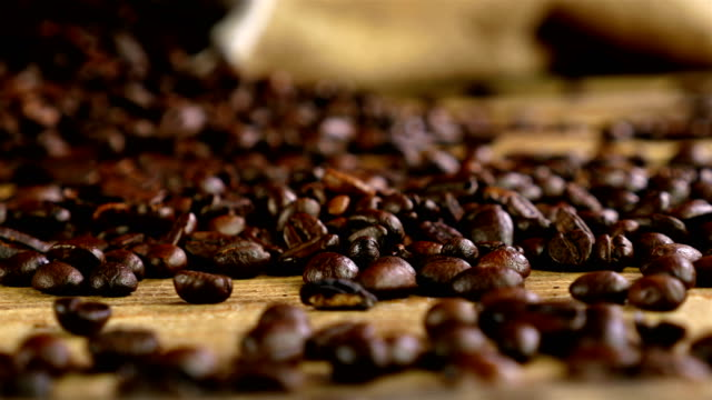 Dolly of scattered coffee beans, bag with coffee beans in the background Dolly of scattered coffee beans, bag with coffee beans in the background hot pockets stock videos & royalty-free footage
