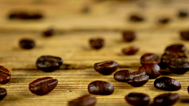 Dolly of scattered coffee beans on wooden table Dolly of scattered coffee beans on wooden table hot pockets stock videos & royalty-free footage