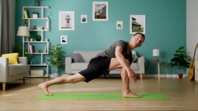 Dolly out of adult man doing yoga in the morning in his living room video