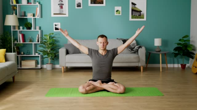 Dolly out of young man doing yoga in the morning in his living room video