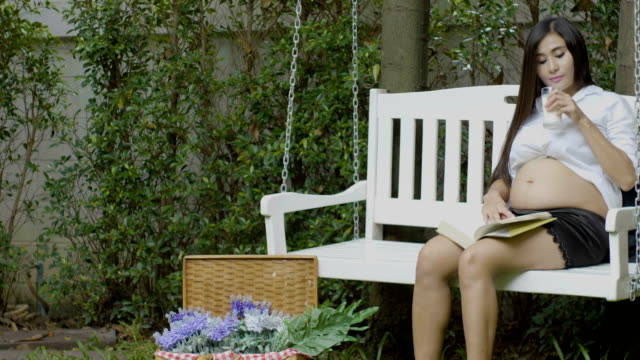 Dolly pregnant woman reading and drink milk in the garden video
