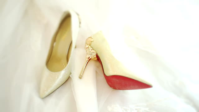 cu dolly right camera : white wedding shoes on wedding dress background. - scarpe video stock e b–roll