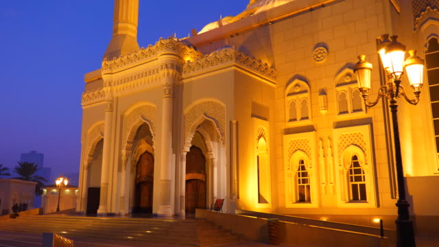 Dolly shot Al Noor Mosque in Sharjah city UAE. Night view illuminated mosque. Islam worship. Gold lights of lantern. Cobalt color of sky.