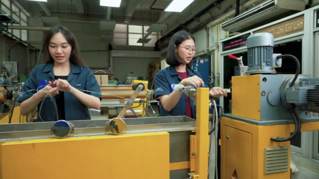 dolly shot: Asian engineer working on polymer production line to produce polymer extrud  by using twin-screw extruder. Woman engineering, scientist student wearing blue clothe doing polymer experiments, discussing with friends. Concept of woman in STEM dolly shot: Asian engineer working on polymer production line to produce polymer extrud  by using twin-screw extruder. Woman engineering, scientist student wearing blue clothe doing polymer experiments, discussing with friends. Concept of woman in STEM manufacturing equipment stock videos & royalty-free footage