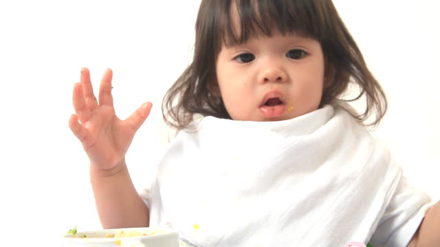 Dolly shot baby is eating by herself on white background video