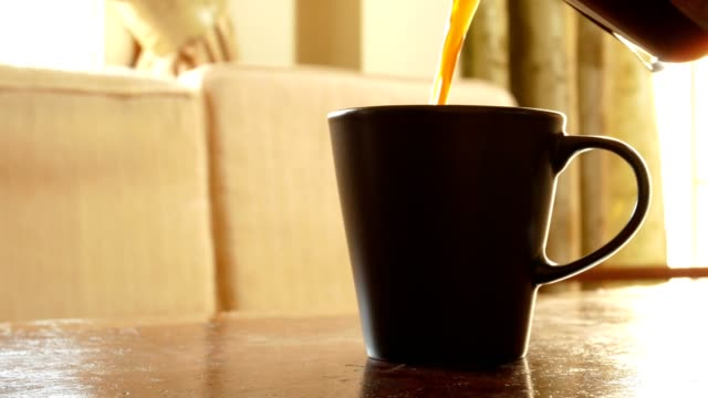 vídeos de stock e filmes b-roll de dolly shot: black coffee pouring into a cup, hand stirring, and picking a cup in living room - home indoor scene - verter