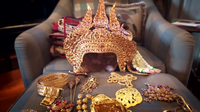 Dolly shot Camera of Ancient golden crown and accessories with gemstones of traditional Thai drama actress.