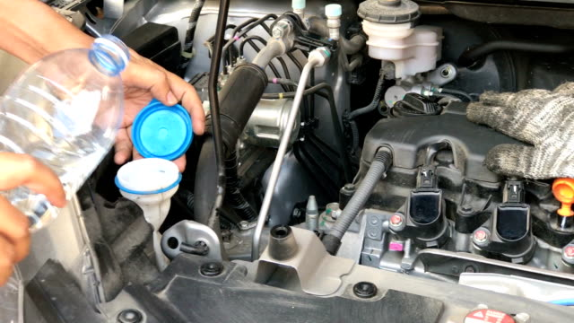 Dolly shot car servicing mechanic pouring water to injection water bottle for glass, component of car engine. video
