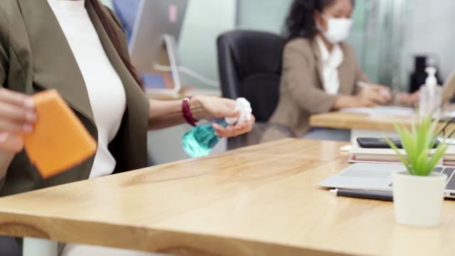 4k uhdドリーショット:新しい正常な社会的距離オフィスでラップトップで動作を開始する前に、ビジネスウーマンの消毒とクリーニングテーブルを閉じます。すべての従業員は、コロナウイル - きれいにする点の映像素材/bロール