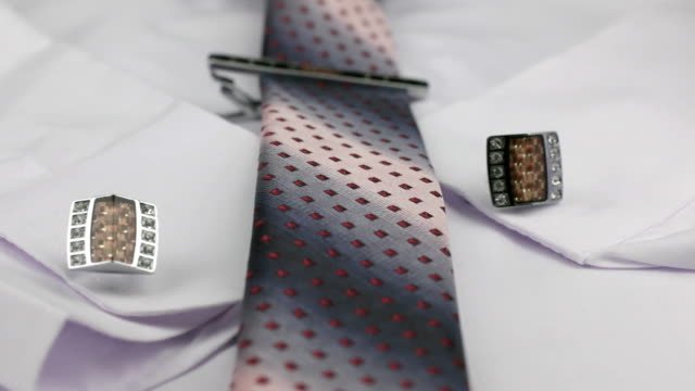 Dolly shot. Close-up knotted pink tie, cufflinks and tie clip on white shirt. video