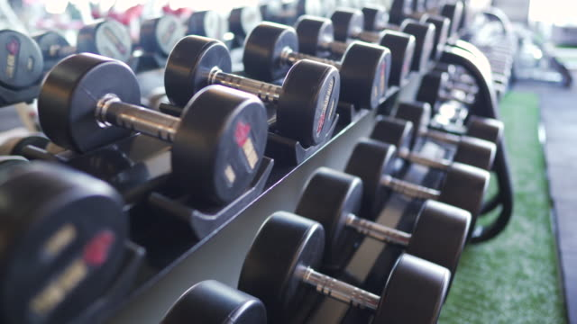 vídeos de stock e filmes b-roll de dolly shot dumbbells in empty gym. - aparelho de musculação