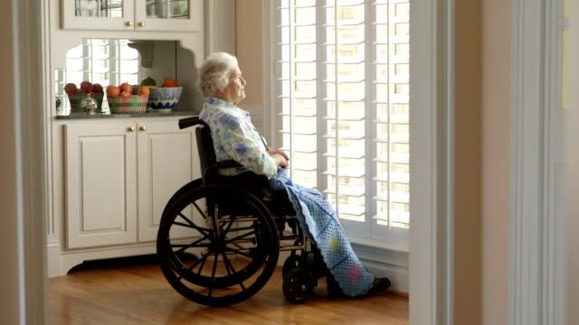Dolly shot Elderly Person in a wheelchair Left to Right Dolly of Elderly Lady in a Wheelchair medicare stock videos & royalty-free footage