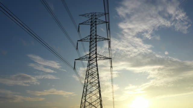 Dolly shot electricity pylons with sunrise