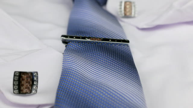 Dolly shot, focus on blue tie, cufflinks, clasp, white shirt. video