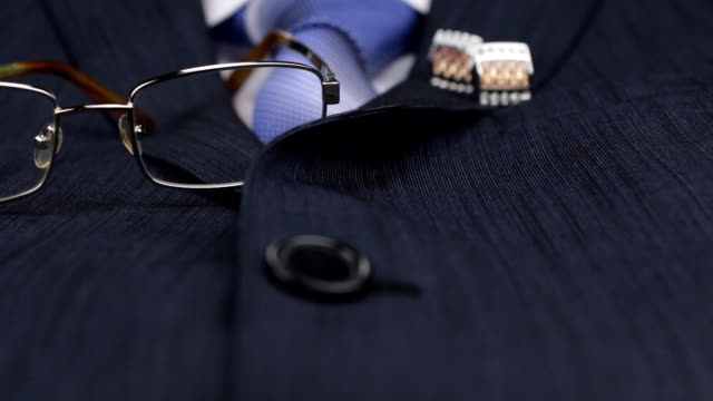 Dolly shot, focus on glasses, tie, cufflinks lies on the suit. video
