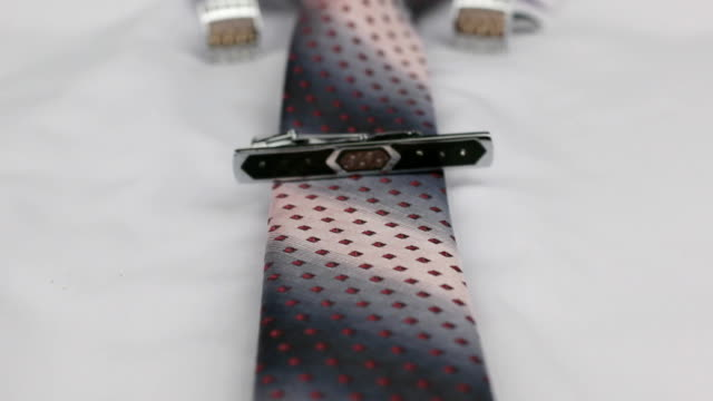 Dolly shot focus on red tie, cufflinks, clasp, white shirt. video