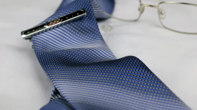 Dolly shot, focus on tie, tie clip, glasses, white shirt. video