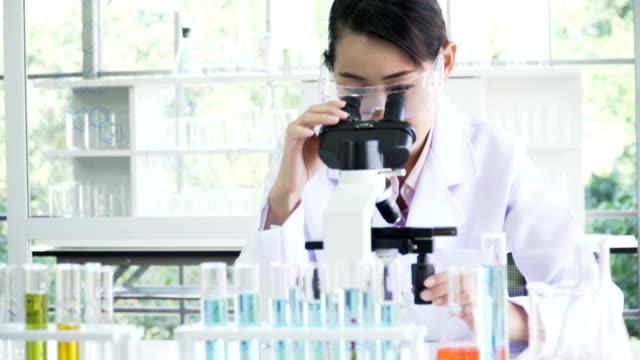stockvideo's en b-roll-footage met dolly schot van vooraanzicht: medio vrouwelijke japanse wetenschapper doet haar onderzoek naar optische microscoop - oost azië