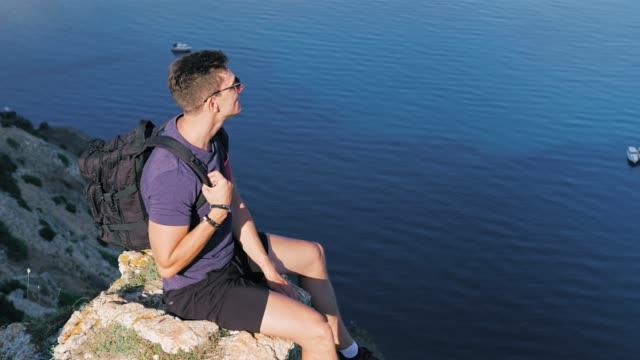 dolly skott manliga backpacker extremt sitter på cliff tittar ner hög vinkel - på gränsen bildbanksvideor och videomaterial från bakom kulisserna