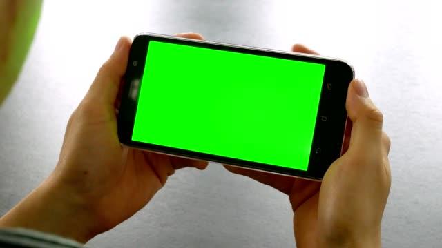 dolly skott: man handen med mobiltelefon med grön skärm för färgtransparens vid office bord - horisontell bildbanksvideor och videomaterial från bakom kulisserna